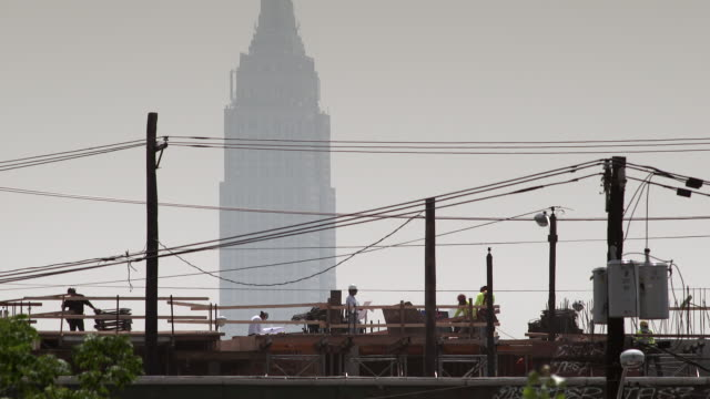 cu of construction workers as they build a new apartment building.  the empire states building in featured behind.  the rebuilding of new york and new jersey after hurricane sandy. - electrical component stock videos & royalty-free footage