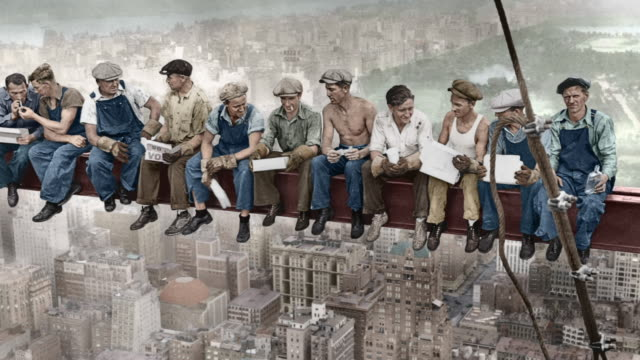 construction workers at the rca building construction site take a lunch break on a steel beam high above manhattan streets. - lunch stock videos & royalty-free footage