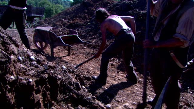 stockvideo's en b-roll-footage met construction workers break up dirt and rocks with pickaxes. - pikken