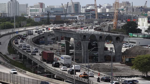 """construction workers build the """"signature bridge,"""" replacing and improving a busy highway intersection at i-95 and i-395 on march 17, 2021 in miami,... - major road stock videos & royalty-free footage"""