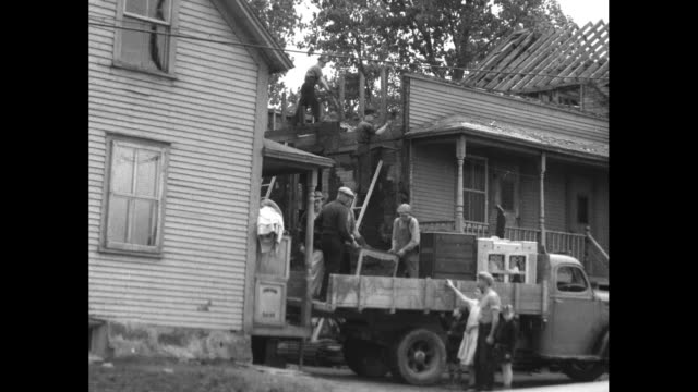 construction workers build woodframe house / man in overalls shakes hands with man in suit / men load truck with household possessions including a... - asbest stock-videos und b-roll-filmmaterial