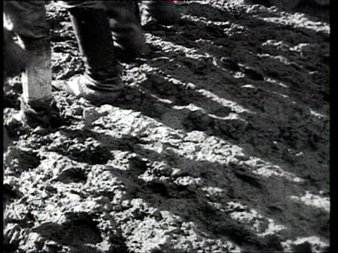 vidéos et rushes de construction workers building dneproges dam workers walking and stomping down on mud / ukraine - 1935