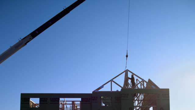 vídeos de stock e filmes b-roll de t/l ws construction workers building house / charlotte, north carolina, usa - guindaste maquinaria de construção