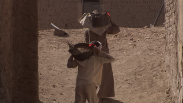 construction workers carry buckets of sand up a small hill. - egypt stock videos & royalty-free footage