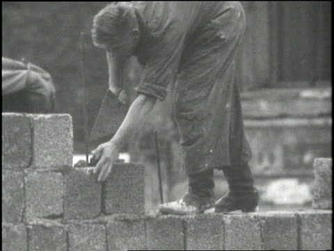 construction workers cement cinder blocks as they build the berlin wall in germany. - building activity stock videos & royalty-free footage