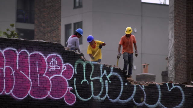 vídeos de stock, filmes e b-roll de construction workers chip away at graffiti painted brick wall on rooftop in brooklyn. - williamsburg new york