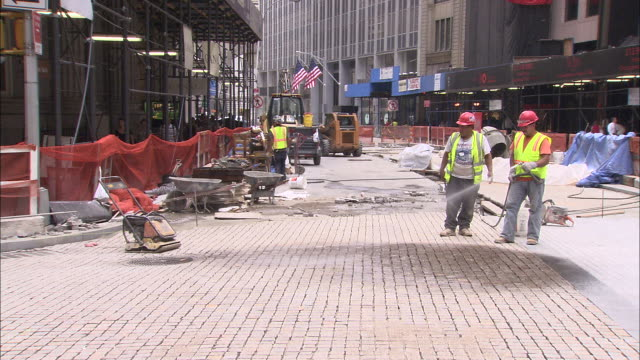 ws construction workers cleaning and fixing cobblestone street in financial district / new york city, new york, usa - cobblestone stock videos & royalty-free footage