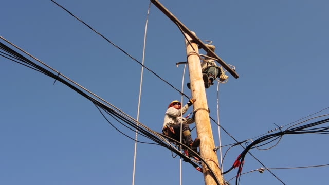 construction workers climb power line - telephone pole stock videos & royalty-free footage