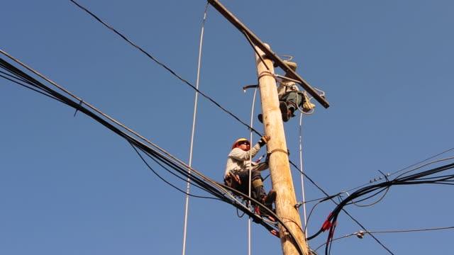 vídeos y material grabado en eventos de stock de construction workers climb power line - poste telegráfico