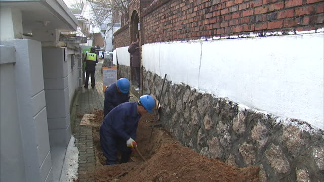 Construction workers digging to restore an old house