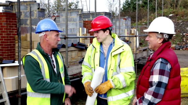 construction workers discussing plans on a building site - construction worker stock videos and b-roll footage