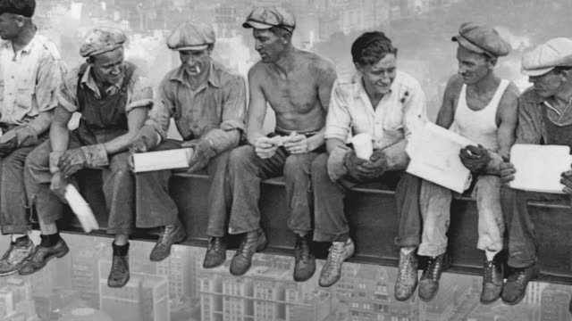 construction workers eat lunch on a girder high in the air at the rca building construction site in new york. - 桁橋点の映像素材/bロール
