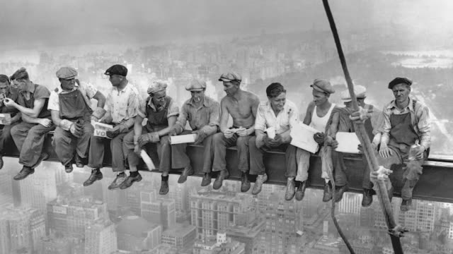 construction workers eat lunch together on a dangerously high girder at the rca building construction site in new york's rockefeller center. - construction worker stock videos & royalty-free footage