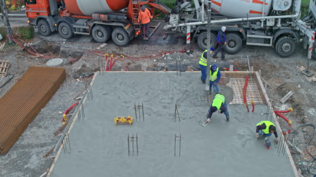 aerial construction workers finishing the foundation at the construction site - concrete stock videos & royalty-free footage
