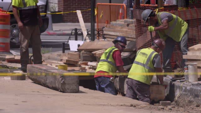 construction workers fit heavy wooden beam into place on new york city street. - reflective clothing stock videos & royalty-free footage