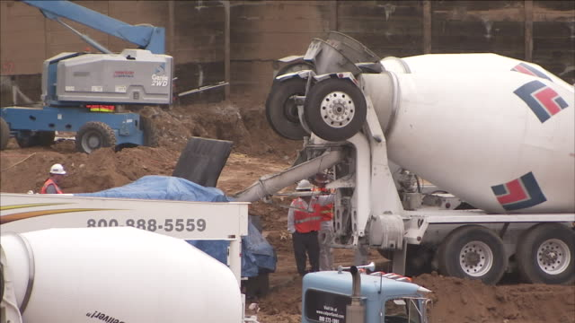 construction workers guide a concrete truck at a pour site. - cement mixer stock videos & royalty-free footage