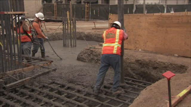 construction workers guide a hose that delivers cement to a re-bar foundation. - zement stock-videos und b-roll-filmmaterial