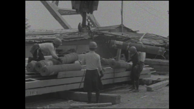 construction workers handle building materials at the base of the tokyo tower project. - tokyo tower stock videos and b-roll footage