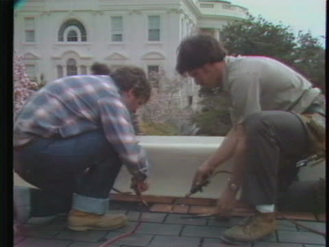 construction workers install solar panels on the roof of the white house. there is an opening medium shot of construction workers working on the... - manual worker stock videos & royalty-free footage