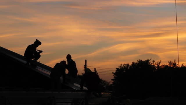 construction workers install steel roof trusses on the construction site. during sunset - safety harness stock videos & royalty-free footage