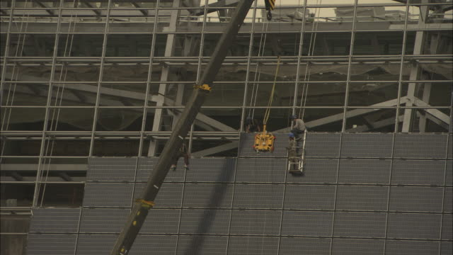 WS Construction workers installing solar photovoltaic panel onto wall of Suntech Power Holdings building, Wuxi, Jiangsu, China