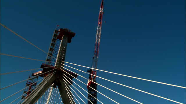 construction workers labor on zakim bridge on a clear day in boston. - ザキム・バンカーヒル橋点の映像素材/bロール