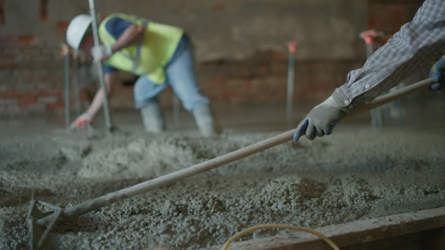 slo mo construction workers lay out freshly poured cement - protection stock videos & royalty-free footage