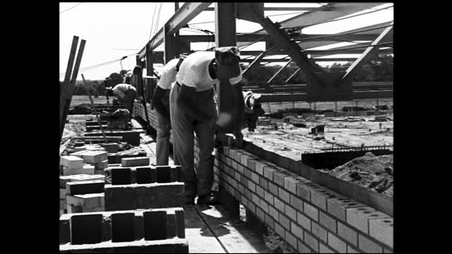 construction workers laying bricks at construction site - 1940 1949 video stock e b–roll