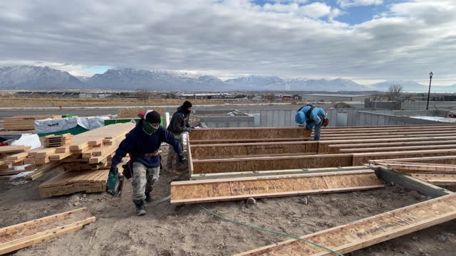vídeos de stock, filmes e b-roll de construction workers laying planks at construction site in lehi, utah, u.s., on wednesday, december 16, 2020. - lehi