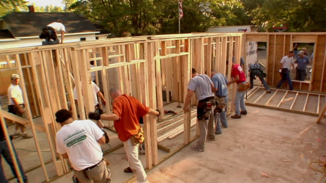 ha ws construction workers lifting frame of new house and positioning it / kalamazoo, michigan, usa - timber stock videos and b-roll footage