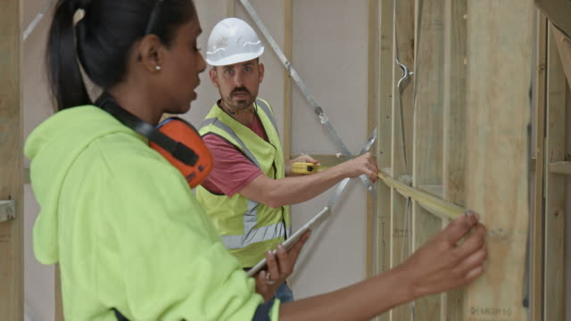 Construction Workers measuring frame at site