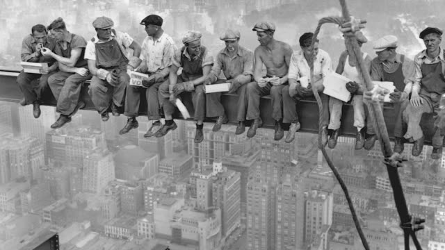 construction workers on break relax on a dangerously high girder at the rca building construction site in new york's rockefeller center. - 桁橋点の映像素材/bロール