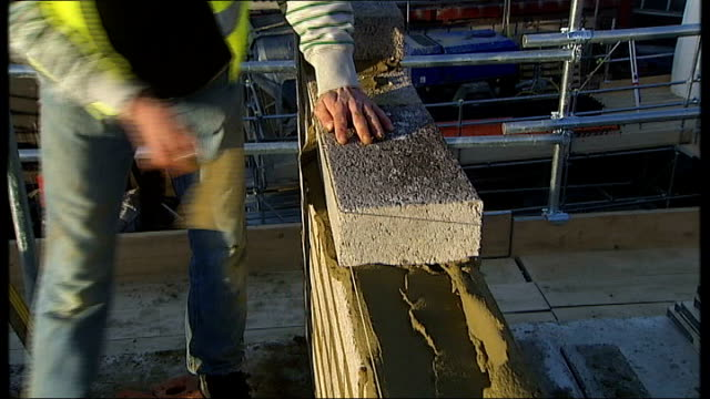 construction workers on building site england london ext various of construction workers on building site as constructing wall smoothing cement... - ピーリング点の映像素材/bロール