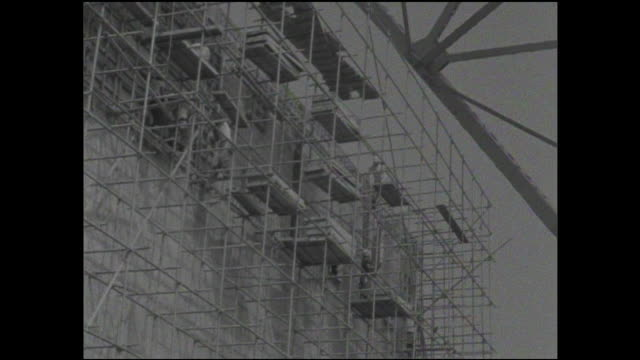 construction workers on scaffolds and platforms build the outer walls of the tokyo tower. - tokyo tower stock videos and b-roll footage