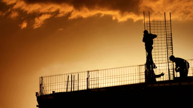 construction workers on top of a building. - in silhouette stock videos & royalty-free footage
