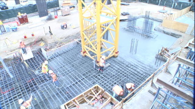 construction workers pour concrete near the base of an antenna. - concrete stock videos & royalty-free footage