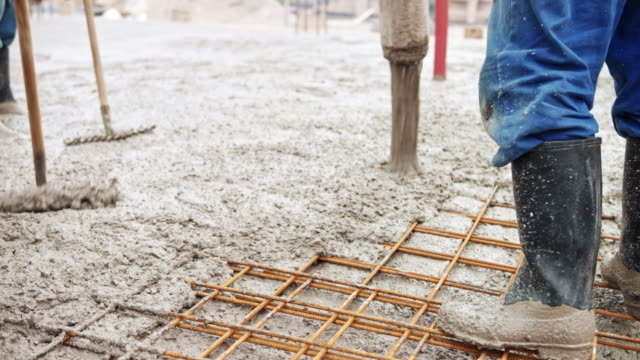 construction workers pouring concrete across the wire mesh - concrete stock videos & royalty-free footage