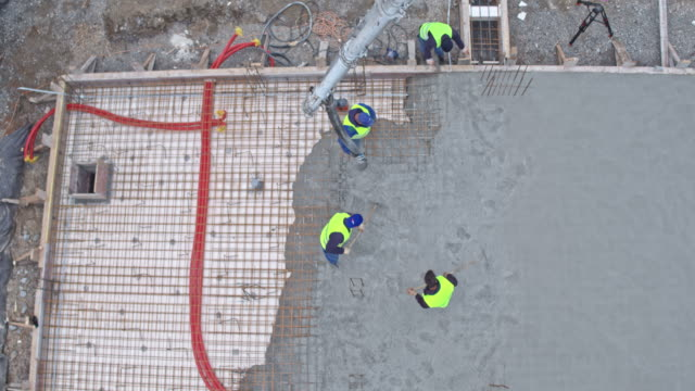 aerial construction workers pouring concrete for the foundation - concrete stock videos & royalty-free footage
