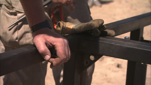 construction workers secure bolts on a steel frame. - bolt stock videos & royalty-free footage