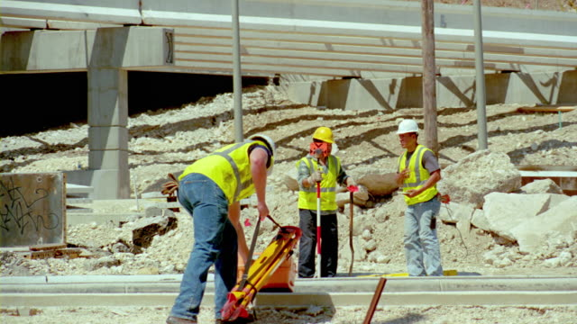 ms, construction workers setting up surveying equipment at construction site, san antonio, texas, usa - einzelne frau mit männergruppe stock-videos und b-roll-filmmaterial