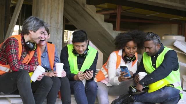 bauarbeiter teilen smartphone in der kaffeepause - arbeiter stock-videos und b-roll-filmmaterial