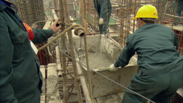 ms tu construction workers supervising tub of cement as it is raised into air by pulley / shenzhen, guangdong, china - セメント点の映像素材/bロール