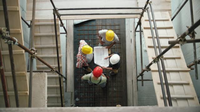 bauarbeiter im gespräch mit der architektin am unteren ende der treppe gerüst und gehen über die pläne - lageplan stock-videos und b-roll-filmmaterial