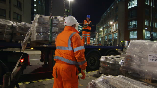 WS Construction workers unloading pallets from truck trailer at night / London, England, United Kingdom