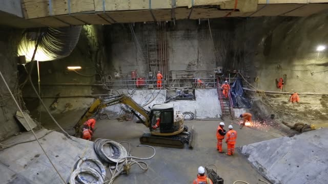 construction workers use a broom and a high pressure water hose as they work inside a tunnel at the stepney green interchange developed by crossrail... - caterpillar inc video stock e b–roll