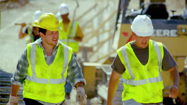 vidéos et rushes de ms, r/f, cu, construction workers walking on site, san antonio, texas, usa - ouvrier du bâtiment