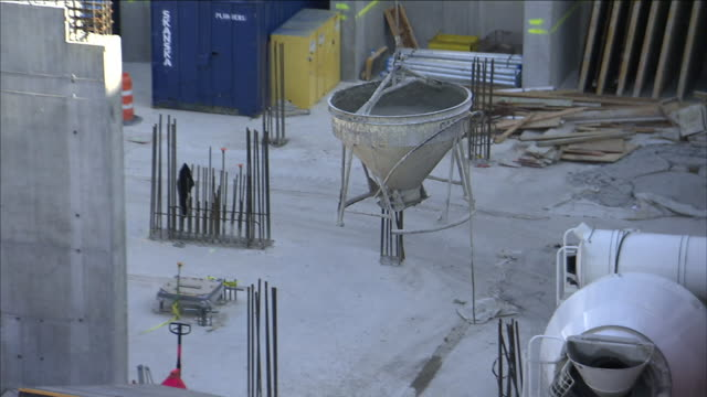 construction workers watch as a crane moves a bucket of concrete into place at a construction site. - cement mixer stock videos & royalty-free footage