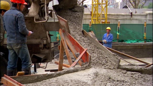 construction workers watch concrete as it pours down a cement mixer chute at a job site. - cement mixer stock videos and b-roll footage