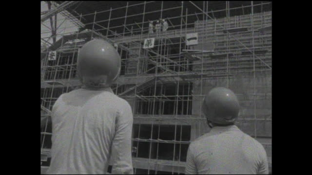 Construction workers wear hardhats as they watch construction of the Tokyo Tower.