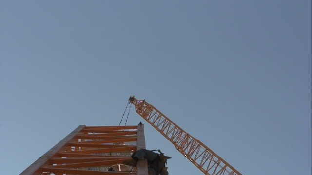 construction workers wear safety equipment as they work to assemble an antenna. - safety equipment stock videos & royalty-free footage
